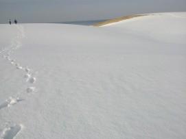 Mer, ciel, sable, neige, deux personnes qui marchent.