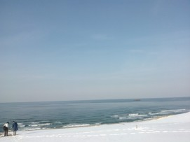 La mer, la neige, les dunes, et deux personnes aux couleurs assorties avec le paysage.